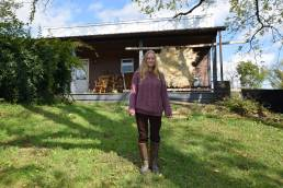 Christine McGuigan stands in front of her cabin in Fresno, Ohio
